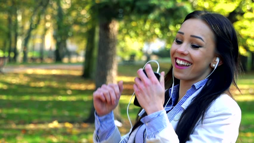 Slowmotion young beautiful woman stands in park, listens to music from mobile ale dances | Shutterstock HD Video #14602744