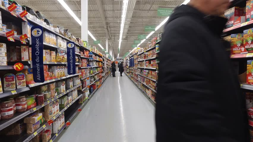MONTREAL, CANADA - FEBRUARY 2016: Walking inside A Walmart aisle with shoppers - Canned goods, crackers, flour etc.