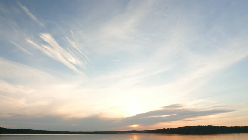 Light stretched clouds over evening sky, lake sunset skies time lapse shot. Sun disk ahead, hide behind dense stripe of clouds, move down to horizon line. Reflex on flat water | Shutterstock HD Video #14637331