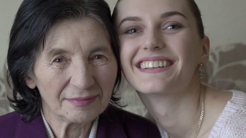 Granddaughter kissing and embracing grandma. Slowly