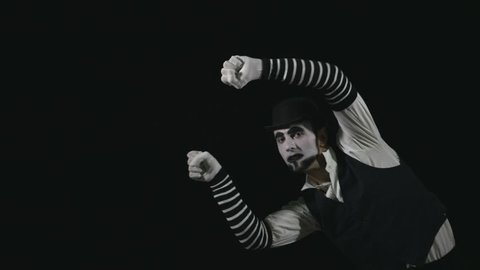 Young funny mime performing a invisible wall act