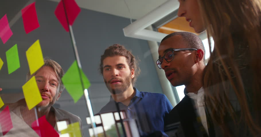 Young modern multi-ethnic group brainstorming in startup office for new business concepts on post it notes on a window