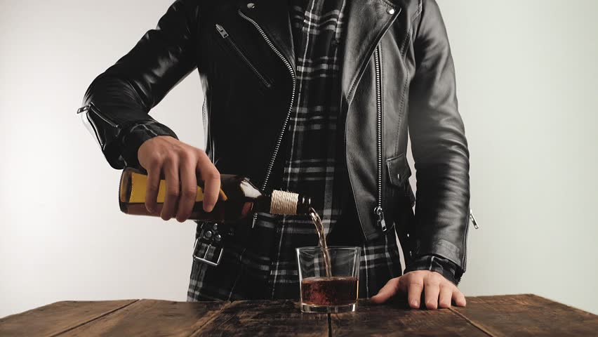 Unrecognizable brutal man in genuine black bike leather jacket pours aged alcohol drink from vintage bottle to whiskey glass on brushed wooden table isolated white background in bar Cinemagraph loop.