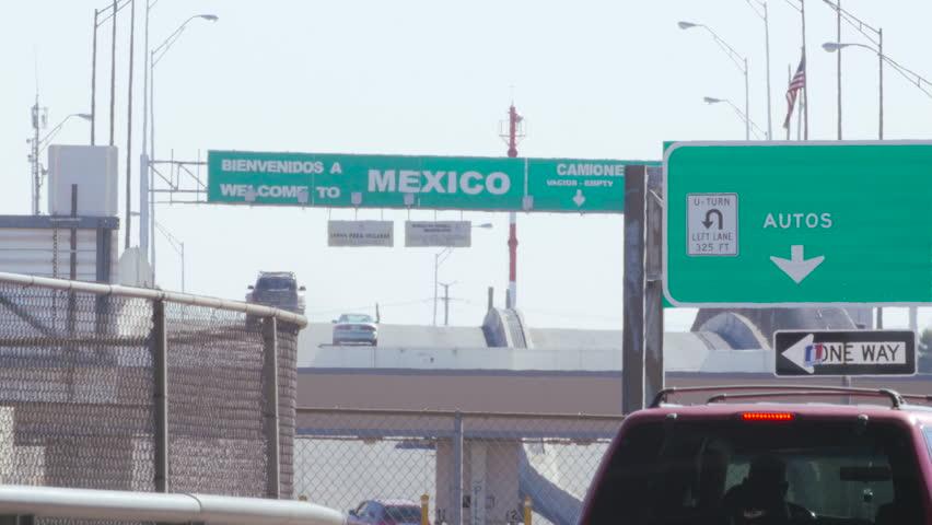 A young man walks toward the border as traffic enters Mexico.