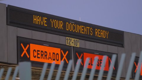 "A lit up sign at the border that says, ""HAVE YOUR DOCUMENTS READY."" to help people migrate between countries."