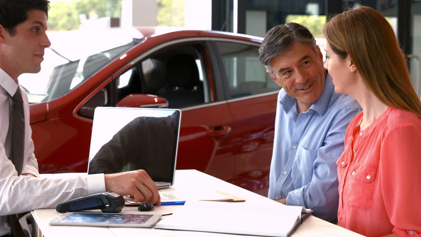 Customers sigining some important documents at the car showroom