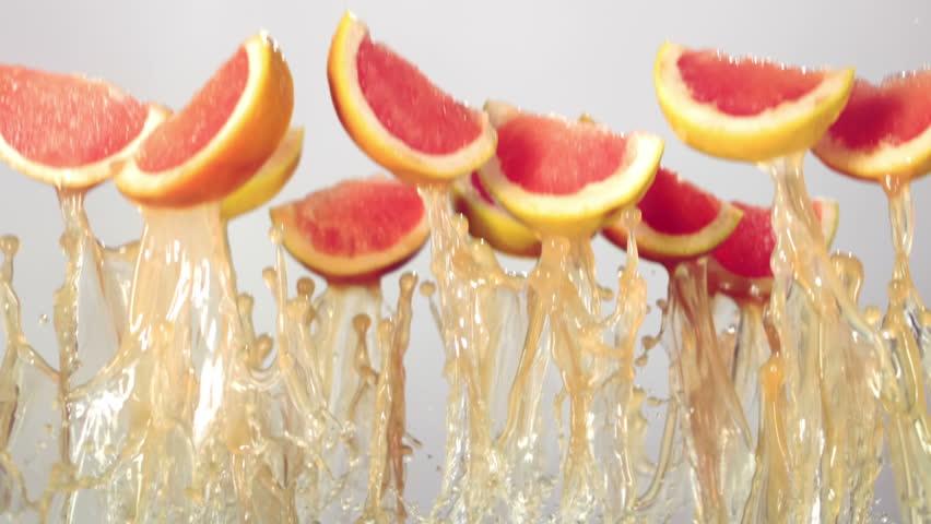 grapefruit slices fly with grapefruit juice, white background, slow motion