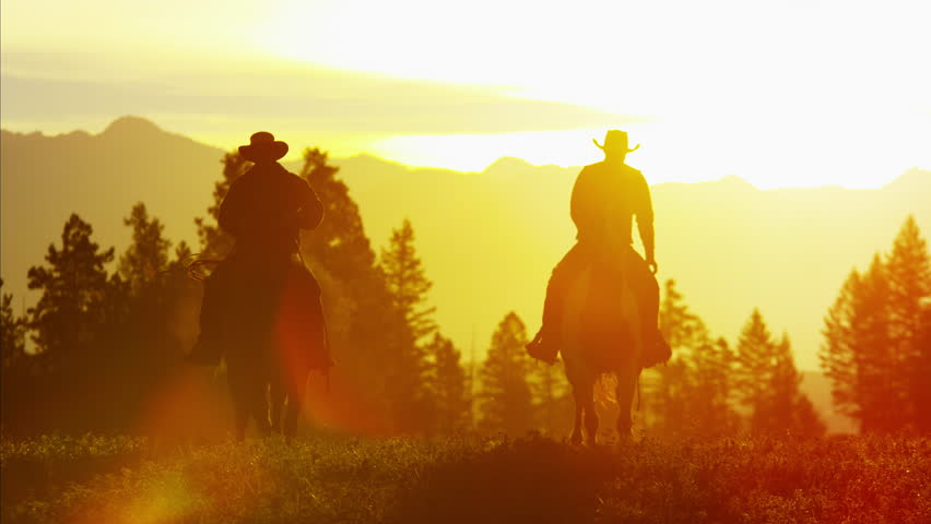 Silhouette reveal of Cowboy Riders in sunset wilderness Canada