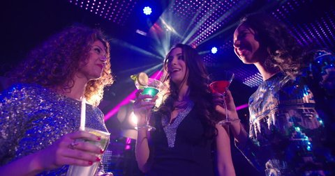 Young attractive Brazilian woman at a nightclub party celebration drinking a cocktail being festive and happy with her multi-ethnic friends