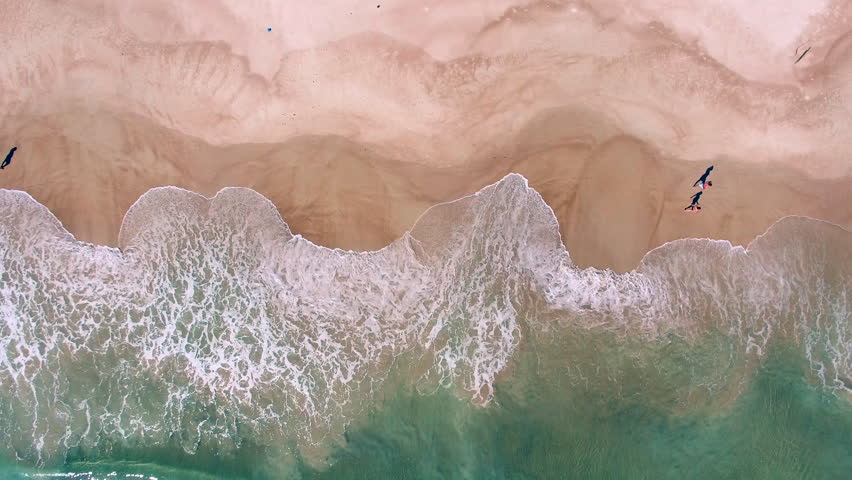 Aerial view of ocean waves crashing on beach with people walking by, 4K drone footage.