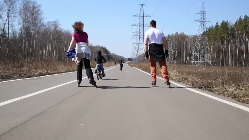 Man and woman riding on roller skates, children riding bicycles on road in park. | Shutterstock HD Video #14743804