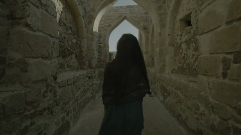 Bahrain Fort, Bahrain - 2012 - Camera tracks back from a veiled woman as she walks with her back to the camera through a vaulted corridor open to the sky .