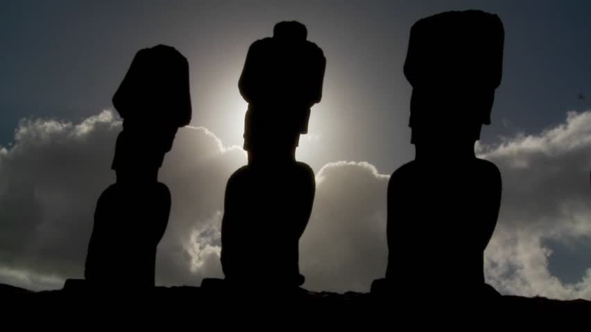 Easter Island statues are silhouetted against the sun.