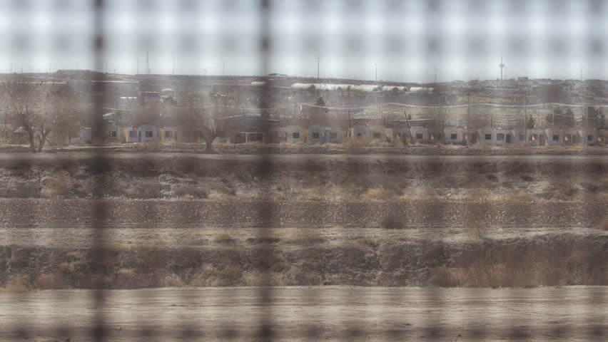 4K pan shot with rack focus looking through the fence between the US and Mexico border.