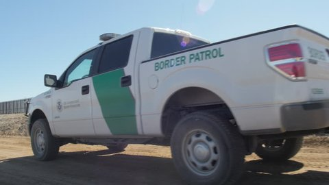 Truck drives past a US Border Patrol truck as it patrols the US and Mexico border on a dirt road in the afternoon.