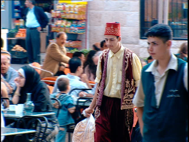 Ehden, Lebanon - 2004 - A Lebanese waiter wears the Lebanese traditional costume of embroidered baggy trousers (Sherwal) an embroidered waistcoat with a Tarboosh - a brimless hat with a tassle.