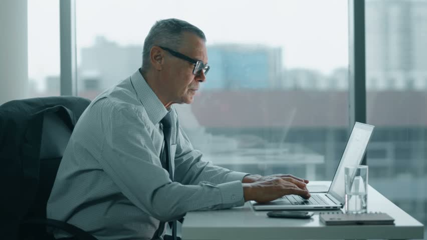 Elderly businessman look at phone and working with computer in modern office | Shutterstock HD Video #14813134