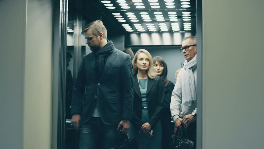 Business people call an elevator, get in when it arrives