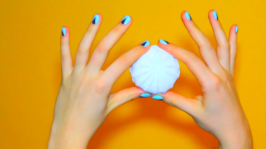 Color woman nails, fashion minimalism manicure. female hands with a trendy hipster  manicure hold marshmallow on orange background.