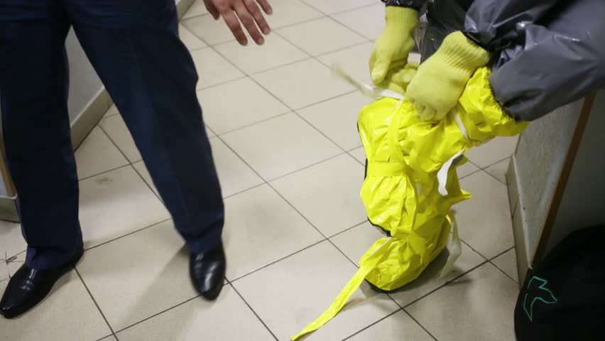 Showing of protective chemical suit - disrobing of yellow shoes