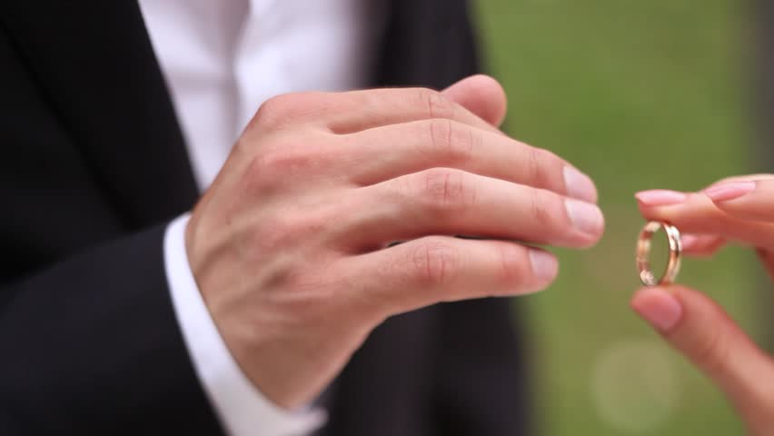Brideu0027s Hand Puts Gold Ring On The Ring Finger Of The Groomu0027s Hands , White  Shirt , Black Jacket Tuxedo, Manicure, Wedding Ceremony On A Sunny Day  Stock ...