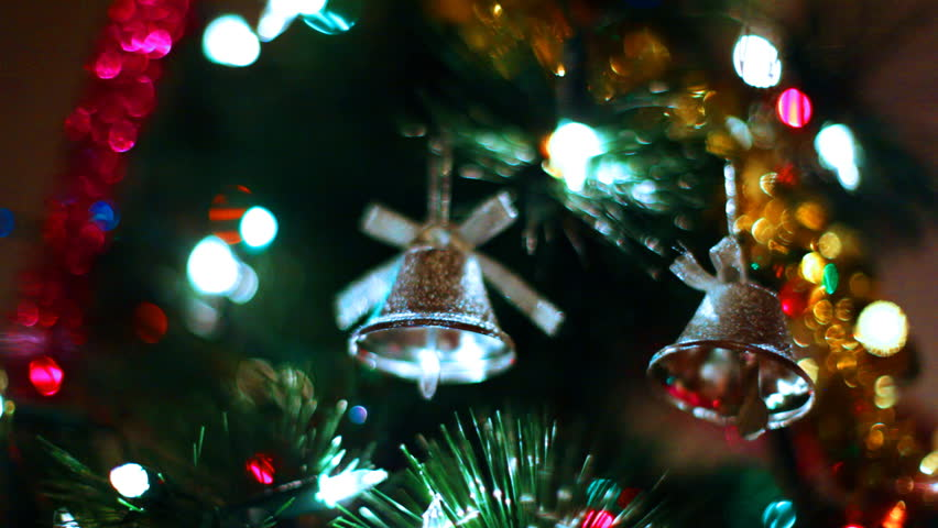 two gold toy bells hang on Christmas tree among of blinking colored garlands, close-up