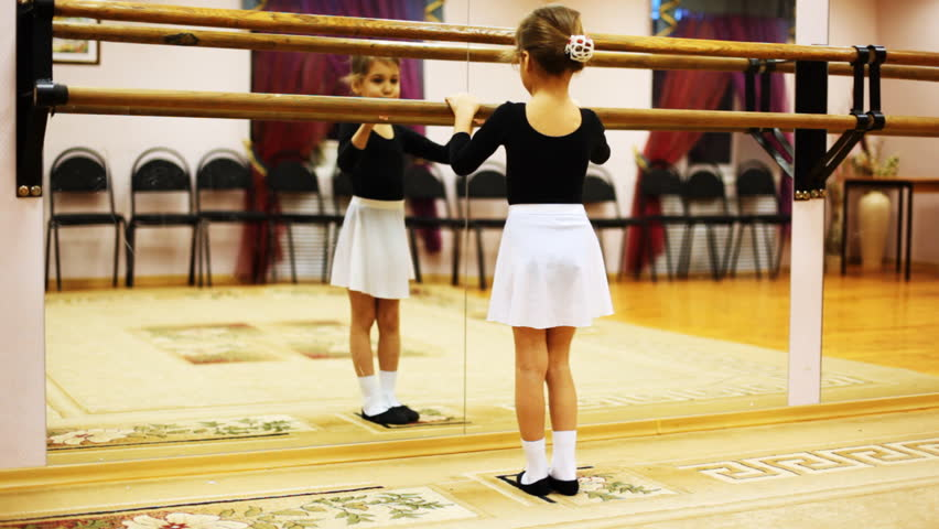 cute little girl does ballet leg movements while facing mirror in dance hall #1484620