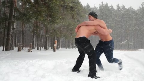 Two bare-chested guys wrestle standing at outdoor sportsground in winter wood.