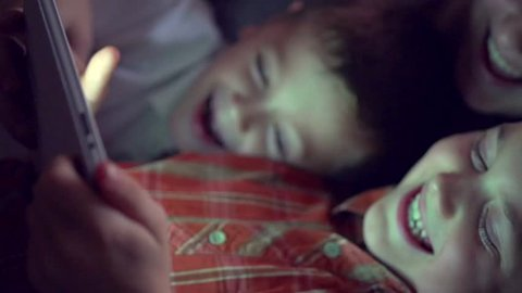 Group of kids using tablet pc at night. Brothers and sister playing games on tablet computer in a dark room, lying on sofa. HD 1080p, slow motion 240 fps, high speed camera
