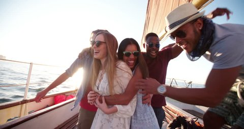 Group of multi ethnic friends standing close to each other on a yacht and posing for a group protrait at sunset