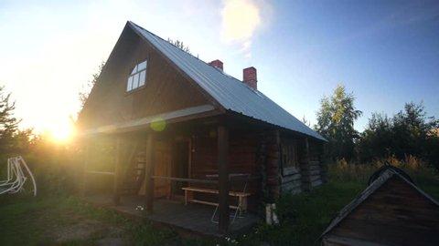 Exterior of wooden russian sauna on the sunset. Beautiful bright sun, peaceful scene.