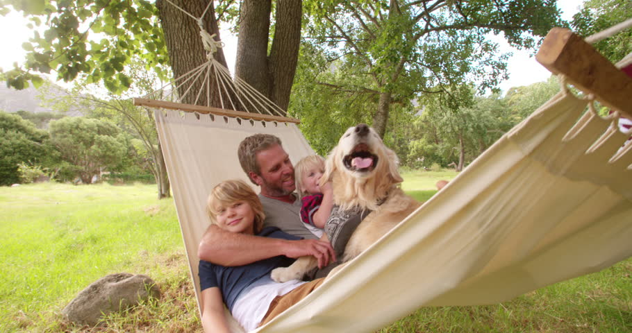 Modern father relaxing and enjoying quality time with his two blonde sons and labrador dog outside in hammock in Slow Motion