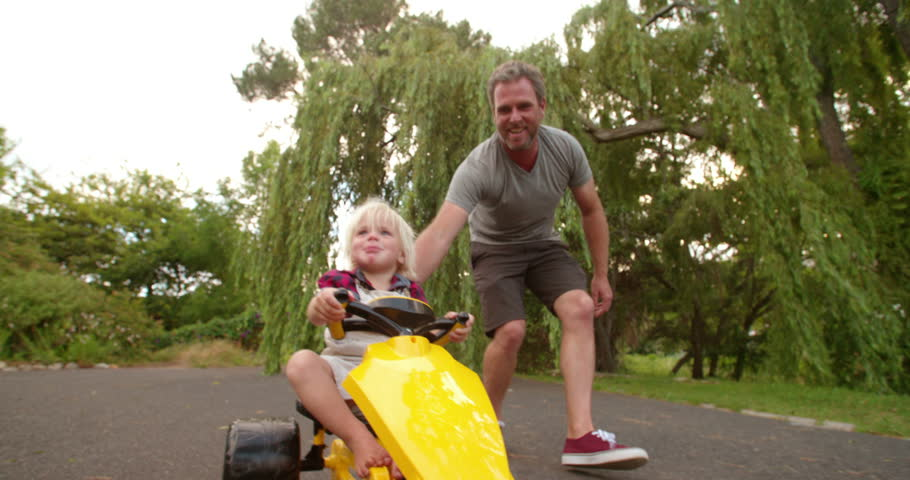 Cheerful father pushing his laughing child in a yellow toy pedal car on the road
