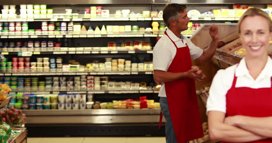 Portrait of smiling worker in front of her colleague in grocery store