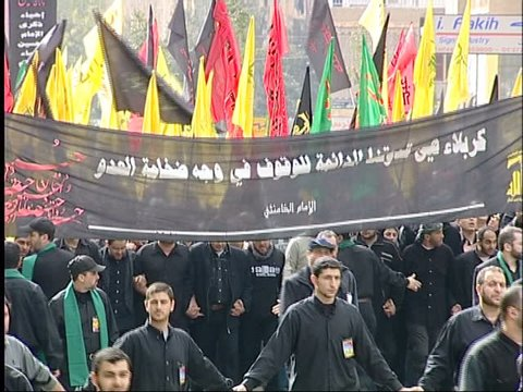 Dahieh, Beirut, Lebanon - 2005 - Hezbollah's Ashoura commemorations. A procession of people dressed in black chant Hezbollah slogans. Men hold a black banner commemorating the Battle of Kerbala.