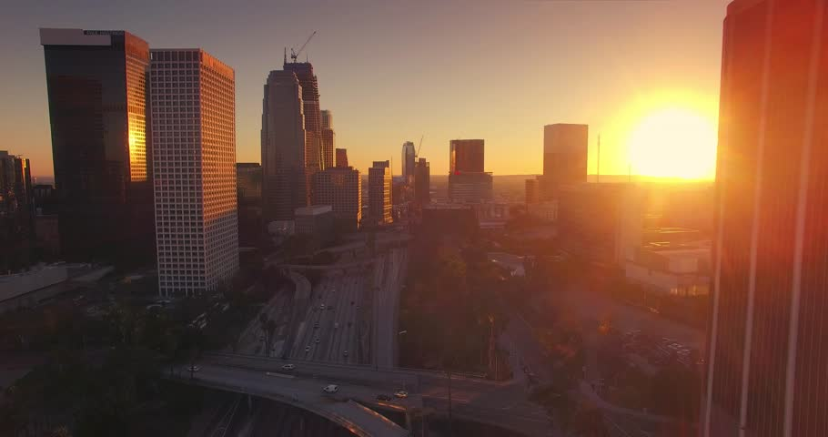 Aerial view of downtown Los Angeles skyline at sunset. Camera flying forward. 4K UHD.