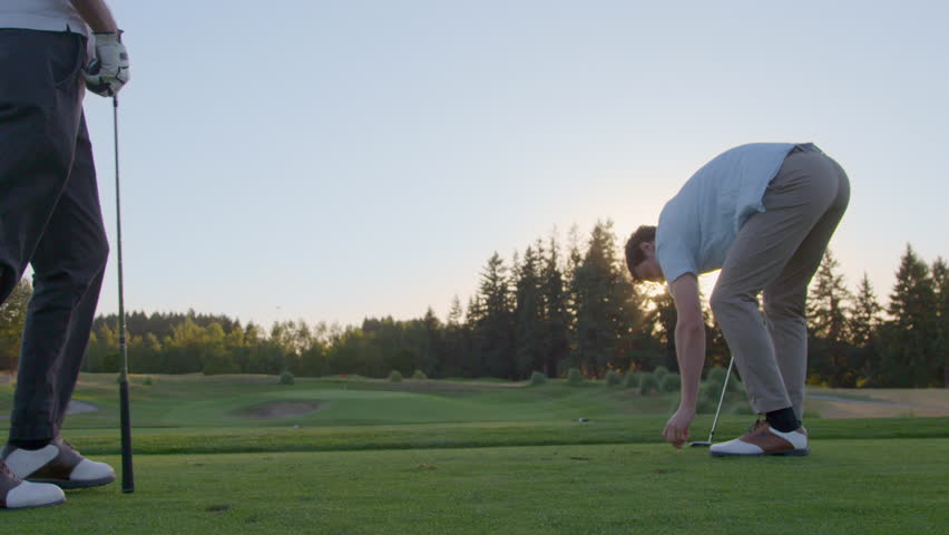 On the tee, a young man offers some tips to his friend, who takes a practice swing