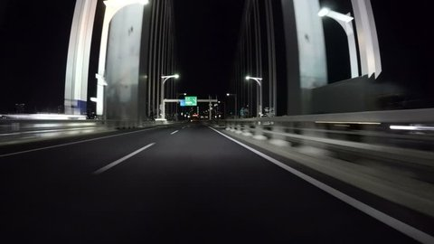 Driver POV over the illuminated Rainbow Bridge heading towards the futuristic lights of Odaiba. Bridge columns glowing white and headlights reflecting on the pavement.