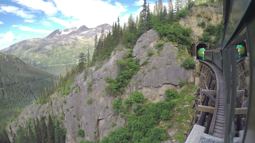 SKAGWAY AK - 2015: White Pass and Yukon Route Railroad Train Crossing Wooden Bridge Into Dark Tunnel with Majestic Mountain Surroundings