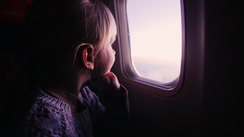 girl looking out the window in the plane