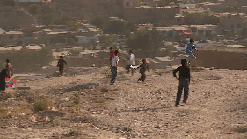 KABUL, AFGHANISTAN - CIRCA 2009: Boys play on the hillsides flying kites in modern circa 2009 in Kabul, Afghanistan. Afghanistan is an impoverished and least developed country, one of the world's poorest.