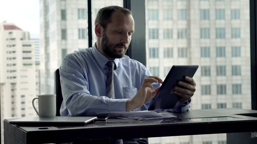Young businessman working with tablet computer in office 