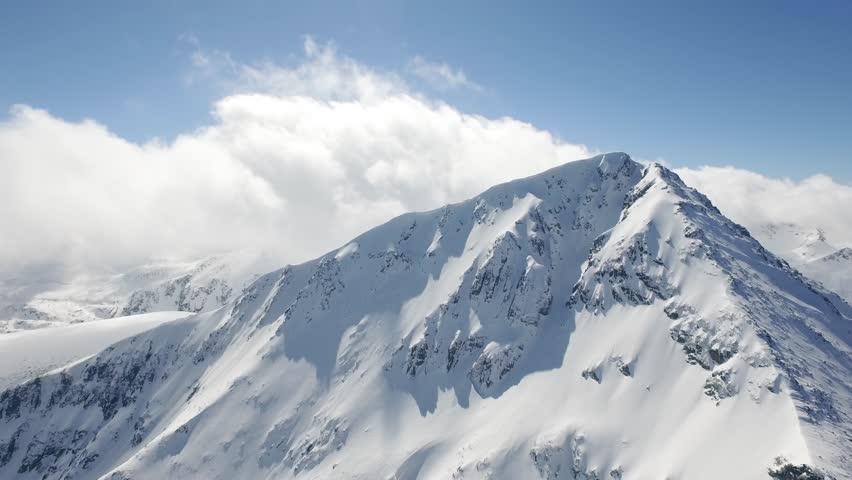Aerial Flight Over Around Snowy Peak Beautiful Blue Sky Clouds Epic Adventure Journey Concept UHD 4K