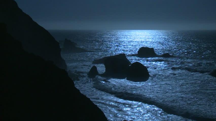 Surf rolls into the Big Sur Coastline of California under a full moon effect.