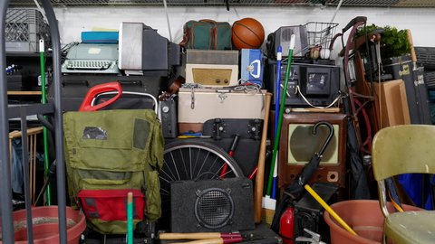 Vintage rummage filled garage dolly out shot.  Object brand names and logos were covered.