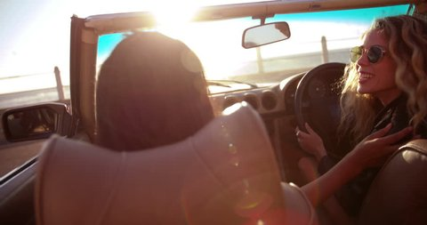 Two happy young girl friends celebrating with raised arms in a convertible parked in front of the beach at sunset