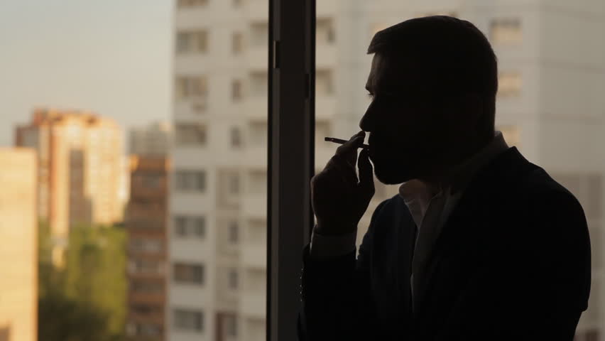 Young man smokes a cigarette at the window | Shutterstock HD Video #15217603