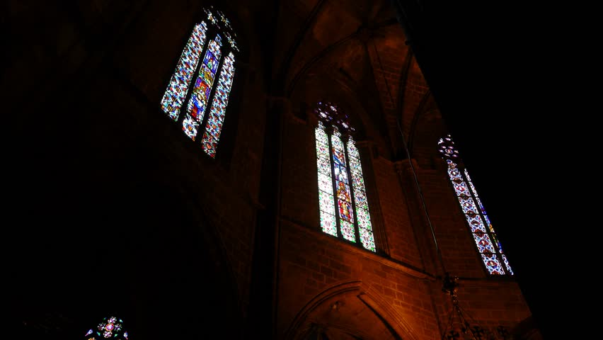 Colorful stained-glass windows at Gothic Cathedral, POV camera move inside, Ambulatory of Saint Eulalia basilica. Low angle shot, look upward to decorated lanced windows, glowing at dark interior.