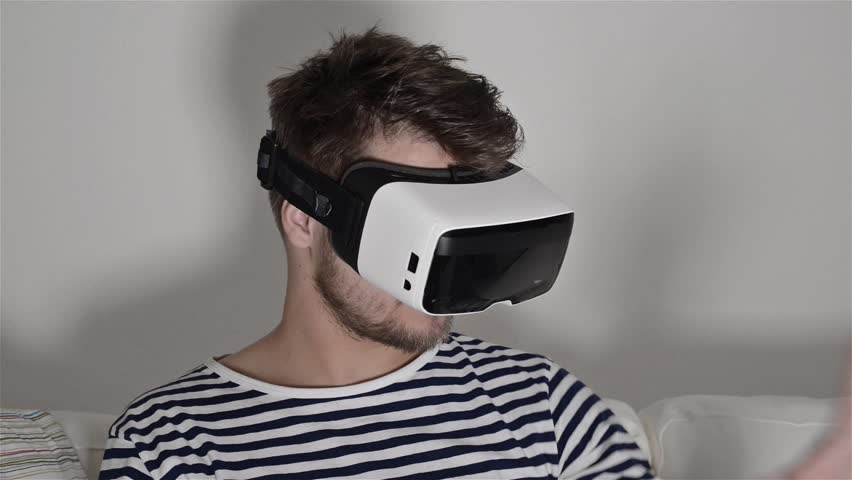 Man wearing virtual reality goggles. Studio shot, white couch