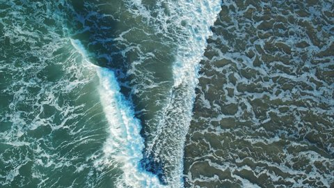 Aerial drone footage of textures being formed by white sea foam. Slow lockdown shot of huge ocean waves crashing on shore. As the waves calm the patterns change. Filmed from an overhead perspective.